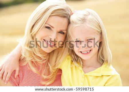 Mother And Daughter Sitting On Straw Bales In Harvested Field - stock photo