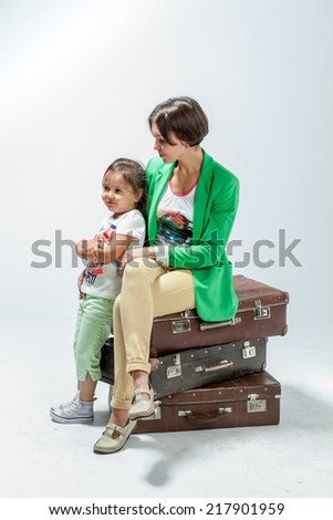 Mother and daughter sitting on suitcases in anticipation of a trip - stock photo