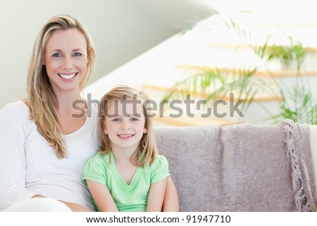Mother and daughter sitting on the couch together - stock photo