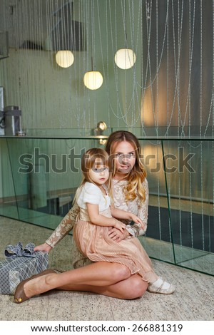 Mother and daughter sitting on the floor in the living room. Near lies a gift for a birthday or Mother's Day. The concept of family happiness. - stock photo