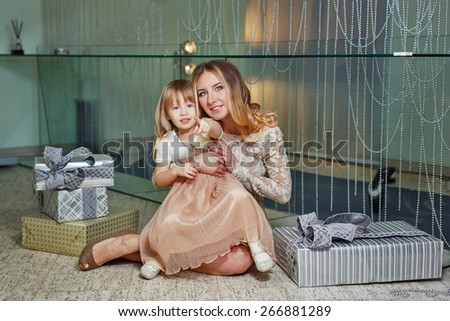 Mother and daughter sitting on the floor in the living room. Next to them are gifts for birthdays and Mother's Day. The concept of family happiness. - stock photo