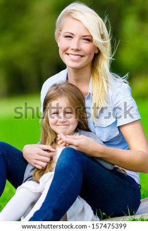 Mother and daughter sitting on the grass embrace each other. Leisure time of happy family - stock photo