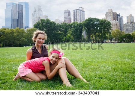 mother and daughter sitting on the grass in the park - stock photo