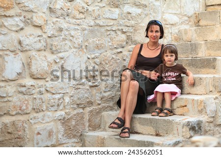 Mother and daughter sitting on the stone stairs looking at the camera - stock photo