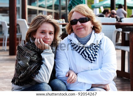 Mother and daughter sitting on the wooden steps to the cafe on the beach - stock photo