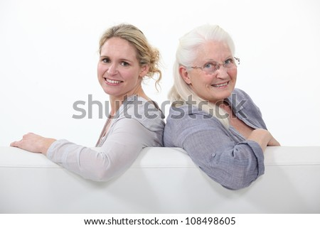 Mother and daughter sitting on white sofa - stock photo