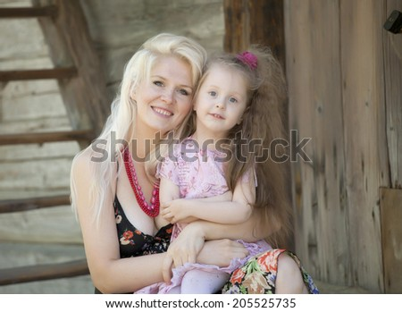 Mother and daughter sitting outside together - stock photo
