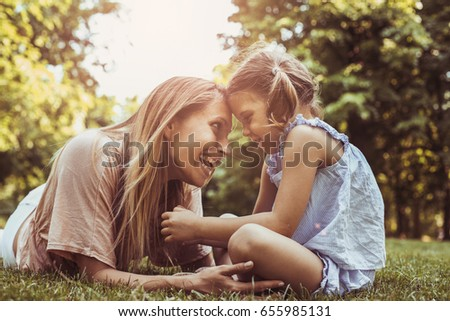Mother and daughter sitting together on green grass. Mother and daughter having funny conversation.