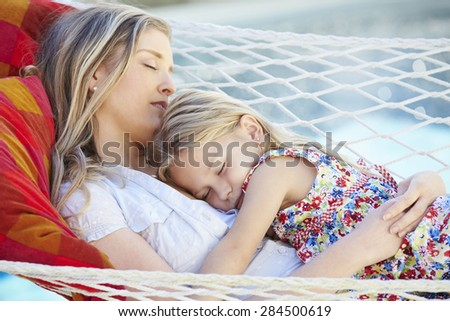 Mother And Daughter Sleeping In Garden Hammock Together - stock photo