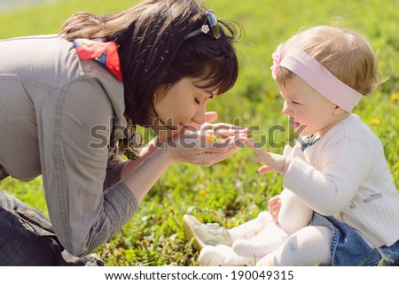 mother and daughter smelling dandelions in her palms - stock photo
