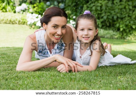 Mother and daughter smiling at camera outside in the garden - stock photo