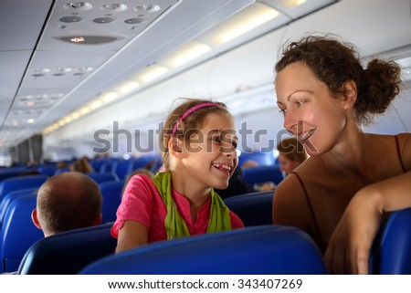 Mother and daughter smiling at each other on an airplane - stock photo
