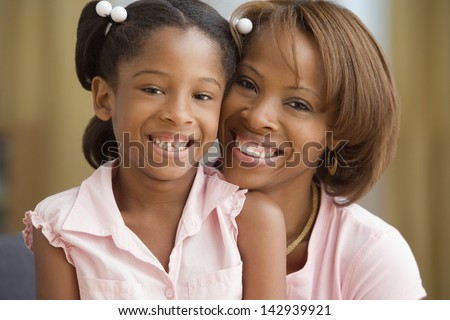 Mother and daughter smiling for the camera - stock photo