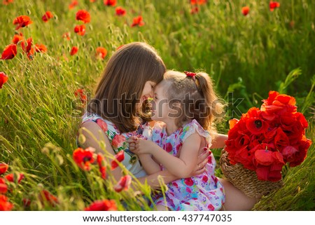 Mother and daughter smiling in a poppy field. The Picnic in the poppy field. Walk with  family in poppy field. The cart poppies - stock photo