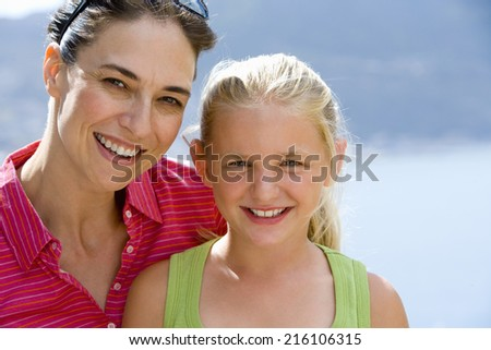 Mother and daughter (6-8), smiling, portrait