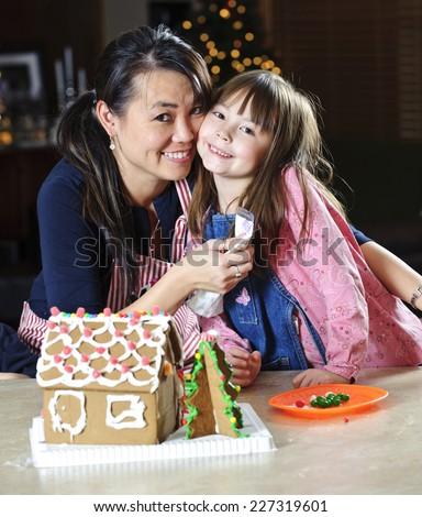 mother and daughter / spending the time together / make gingerbread house - stock photo