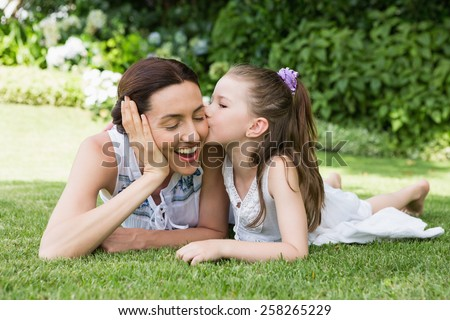 Mother and daughter spending time outside in the garden - stock photo