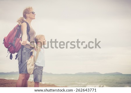 Mother and daughter standing  on the beach at the day time. Concept of friendly family. - stock photo