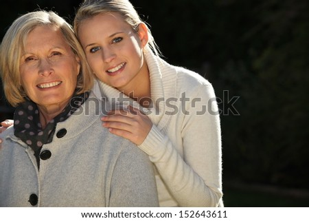 Mother and daughter stood together - stock photo