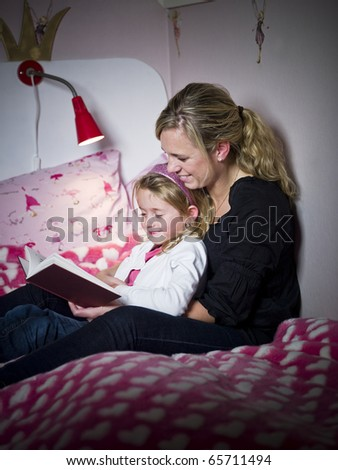 Mother and Daughter storytelling sitting on the bed - stock photo