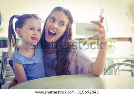 Mother and daughter taking selfie at cafe terrace on a sunny day - stock photo