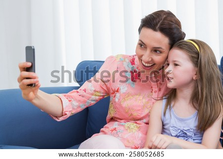 Mother and daughter taking selfie at home in the living room