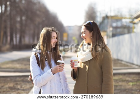 Mother and daughter talking, laughing and smiling on the street, drinking coffee in cups, in the fall or spring day, happy family. - stock photo