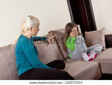 Mother and daughter talking on the couch at home