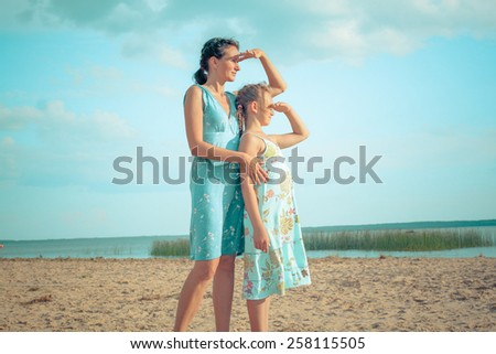 mother and daughter teenager standing and hugging on the coast