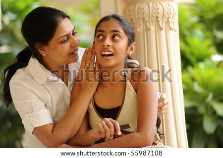 mother and daughter telling secret - stock photo