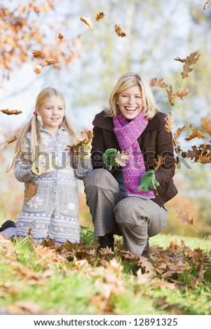 Mother and daughter throwing autumn leaves in the air - stock photo