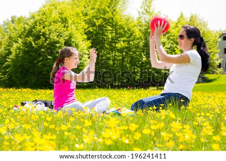 Mother and daughter throwing ball to each other in the park - stock photo