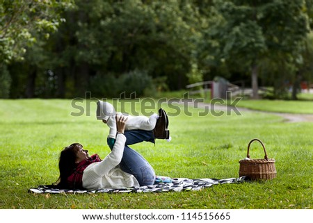Mother and daughter together. Lying in park. - stock photo