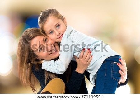 Mother and daughter together on unfocused background