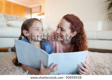 Mother and daughter together with periodical on the floor - stock photo