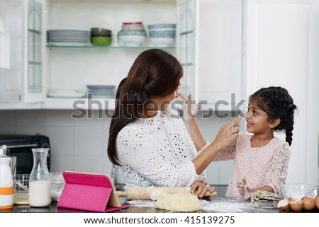 Mother and daughter trying to smear flour on noses of each other - stock photo