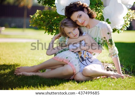 mother and daughter under a tree with clouds