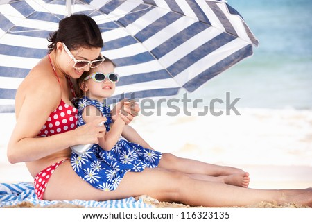 Mother And Daughter Under Beach Umbrella Putting On Sun Cream - stock photo