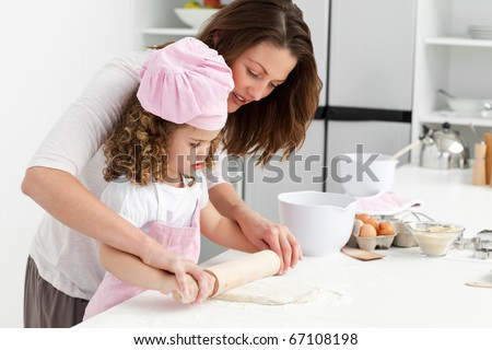 Mother and daughter using a rolling pin together in the kitchen