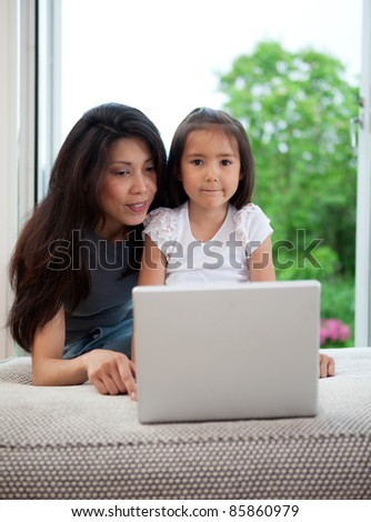 Mother and daughter using computer together in a home interior - stock photo