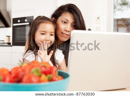 Mother and daughter using computer, waving while in a live video chat - stock photo