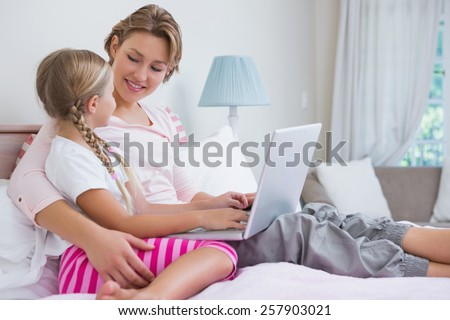 Mother and daughter using laptop in bed at home in the bedroom