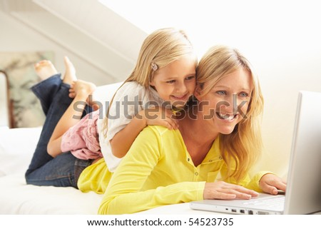 Mother And Daughter Using Laptop Relaxing Sitting On Sofa At Home