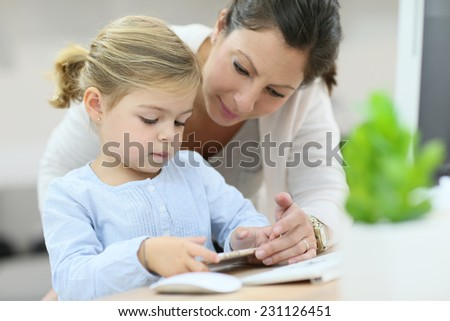 Mother and daughter using smartphone, home office - stock photo