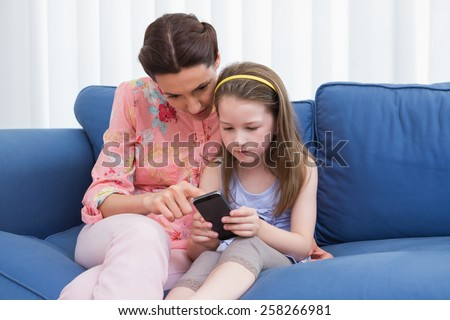 Mother and daughter using smartphone on couch at home in the living room - stock photo