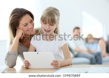 Mother and daughter using tablet at home - stock photo