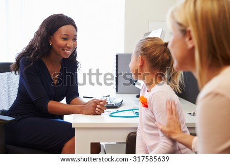 Mother And Daughter Visiting Doctor In Surgery - stock photo