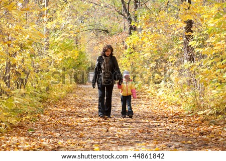 Mother and daughter walk on foot on autumnal park