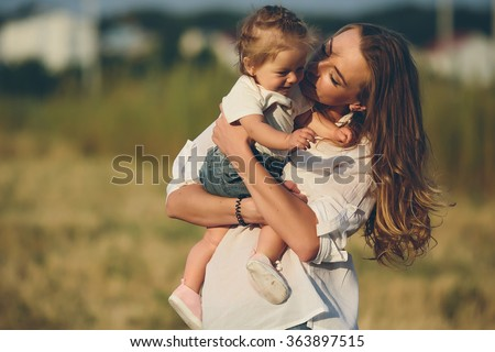 mother and daughter walk together on a rural road - stock photo