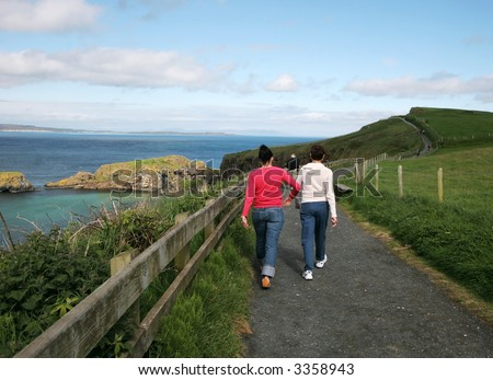 mother and daughter walking along pathway surrounded by beautiful landscape - stock photo